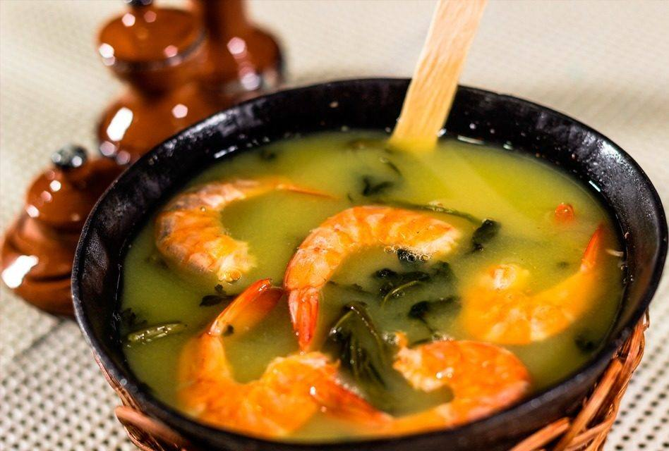 """It consists of a mixture containing tucupi, cooked tapioca gum, jambu and dried shrimp. Of indigenous origin, tacacá is an almost liquid porridge served in bowls and sold by """"tacacazeiras"""". Usually at dusk, on the corner of the main streets of the cities of Pará."""